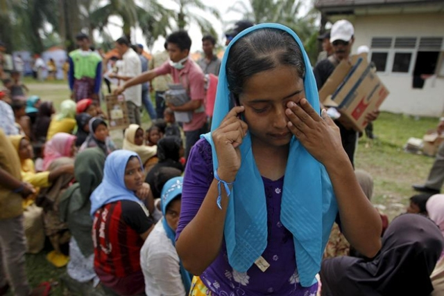 "A Rohingya migrant woman, who recently arrived in Indonesia by boat, cries as she talks on the phone to her mother in Malaysia, inside a temporary compound for refugees in Aceh Timur regency, Indonesia's Aceh Province May 22, 2015.  Myanmar's military commander-in-chief said some ""boat people"" landing in Malaysia and Indonesia this month are likely pretending to be Rohingya Muslims to receive U.N. aid and that many had fled neighbouring Bangladesh, state media reported on Friday. REUTERS/Beawiharta - RTX1E2VV"