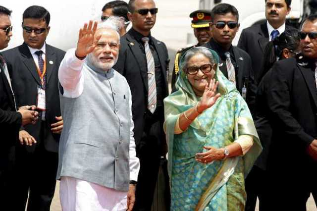 India's Prime Minister Narendra Modi waves with Bangladesh's Prime Minister Sheikh Hasina at Shahjalal International Airport in Dhaka June 6, 2015. Modi arrived in Dhaka for a two-day state visit to Bangladesh. REUTERS/Rafiqur Rahman