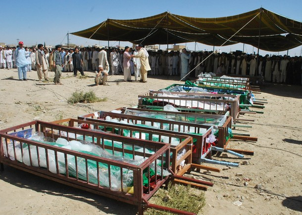 Pakistani Shiite Muslims gather beside coffins of community members in Quetta on September 21, 2011, after their killing by gunmen. Gunmen shot dead 26 Pakistani Shiite Muslim pilgrims travelling to Iran on September 20, the deadliest attack on the minority community in Pakistan for more than a year, officials said. In a brutal assault, gunmen ordered pilgrims off their bus, lined them up and assassinated them in a hail of gunfire in Mastung, a district 50 kilometres (30 miles) south of Quetta, the capital of the southwest Baluchistan province. AFP PHOTO/BANARAS KHAN (Photo credit should read BANARAS KHAN/AFP/Getty Images)
